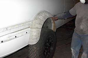 Shop built fiberglass fender flare being fitted to cover 12.5 inch wide tires on a Sprinter